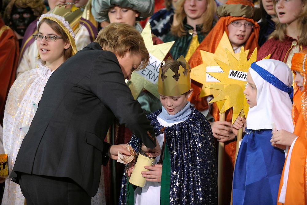 04 JUN 2008, BERLIN/GERMANY:<br /> Angela Merkel, CDU, Bundeskanzlerin, steckt ihre Spende in die Spendendose von einem der Heiligen drei Koenige, waehrend dem Empfang der Sternsinger im Bundeskanzleramt<br /> IMAGE: 20080104-01-027<br /> KEYWORDS: Heilige drei Koenige, Heilige drei Könige, spendet, Geld, Geldscheine, Kanzleramt