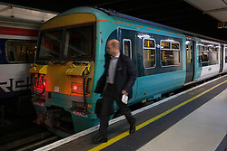 © under license to London News Pictures. 02/01/14. An average 2.8% increase in rail fares comes into effect on Thursday 2nd Jan 2014, pushing the cost of some commuter travel to more than £5,000 a year. FILE PICTURE DATED:  London, UK 28/11/2012. A passenger walking to a train at Victoria Train Station. Rail fares set to increase by an average of 4.2% in January, a watchdog has revealed. Photo credit: Tolga Akmen/LNP