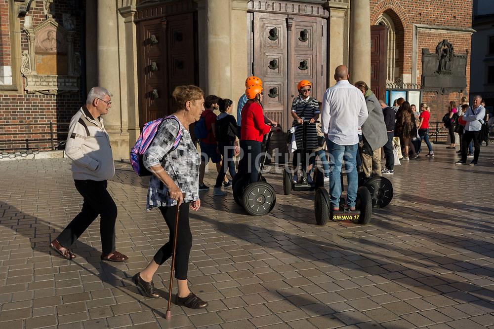 Tourist on Segways listen to their tour guide outside the Church of St Mary on Rynek Glowny market square, on 22nd September 2019, in Krakow, Malopolska, Poland.