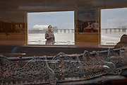 Open Editions Prints<br /> Woman pauses for a smoke on a Blackpool England pier with window reflections and Victorian Ironwork seat and rail with distant pier visible in background
