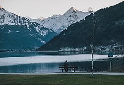 19.03.2020, Zell am See, AUT, tägliches Leben mit dem Coronavirus, im Bild ein Mann sitzt auf einer Bank und genießt die Abendstimmung am Zeller See und den Blick auf Zell am See. Die Abendsonne strahlt den schneebedeckten Gipfel des Kitzsteinhorn an. Für ganz Österreich wurde eine Ausgangsbeschränkung der Bundesregierung ausgesprochen // Evening atmosphere at the Zeller See with a view of Zell am See. The evening sun shines on the snow-covered summit of the Kitzsteinhorn. The Austrian government is pursuing aggressive measures in an effort to slow the ongoing spread of the coronavirus, Zell am See, Austria on 2020/03/19. EXPA Pictures © 2020, PhotoCredit: EXPA/ Stefanie Oberhauser