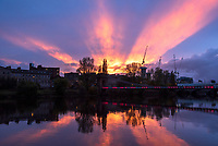 Sun beams spread across the sky as the sun sets over Glasgow's River Clyde
