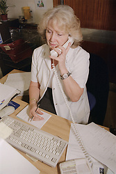 Medical ward receptionist sitting at desk in front of computer talking on telephone,
