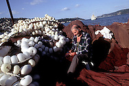 ISTANBUL, TURKEY.  A fisherman tends to his nets along the banks of the Bosphorus in Istanbul, Turkey. August 1999.