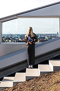 A young girl stands on the stairway on the upper part of the urban mountain and views over Copenhagen skyline.