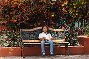 A young girl sits on a park bench in the town of Valle de Angeles, Honduras on Friday April 26, 2013.