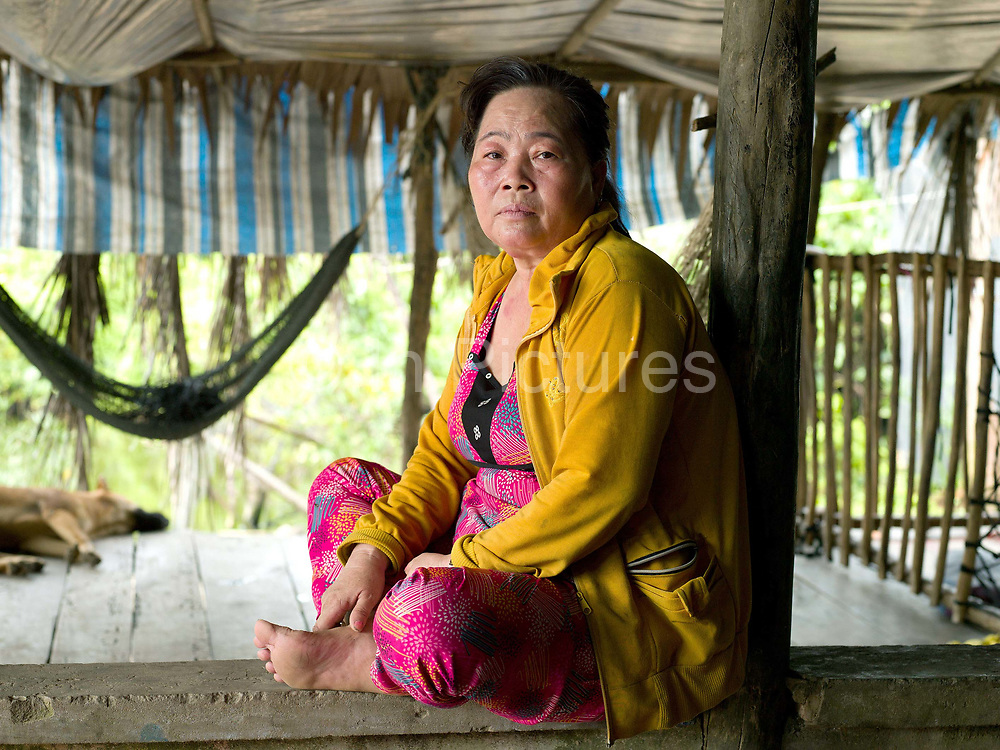"""Hien Thi Tran (55) lives with her extended family in Number 1 Village, Khanh Hoi commune, in the southern province of Ca Mau in Vietnam's Mekong Delta. The coastal village is extremely vulnerable to rising sea levels, salt water intrusion and climate change, which are disrupting the lives of farming and fishing-dependent communities throughout the low-lying Delta. Hien says: """"When we first moved to this farm 10 years ago it was good living. But now it gets worse and worse because the sea keeps flooding in. Every year our rice fields flood and sometimes the water even comes into the house as high as my knee. We have to pump it out. We used to grow rice and vegetables but for the last few years this has been impossible – the soil is very salty."""""""