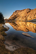 Alpenglow at sunset on Fletcher Peak reflected in Vogelsang Lake, Yosemite National Park, California