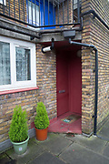 A burgundy front door at Cressingham Gardens estate on 22nd February 2017 in South London, United Kingdom. Cressingham Gardens is a council garden estate in Lambeth. Located on the southern edge of Brockwell Park, it comprises of 306 dwellings. It was designed at the end of the 1960s by the Lambeth Borough Council architect Edward Hollamby, and built at the start of the 1970s. In 2012 Lambeth Council proposed regeneration of the whole estate, a decision highly opposed by many residents and a campaign to stop the redevelopment has been in place since.