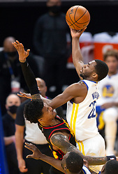 Mar 26, 2021; San Francisco, California, USA; Golden State Warriors forward Andrew Wiggins (22) shoots over Atlanta Hawks forward John Collins (20) during the first quarter of an NBA basketball game at Chase Center. Mandatory Credit: D. Ross Cameron-USA TODAY Sports