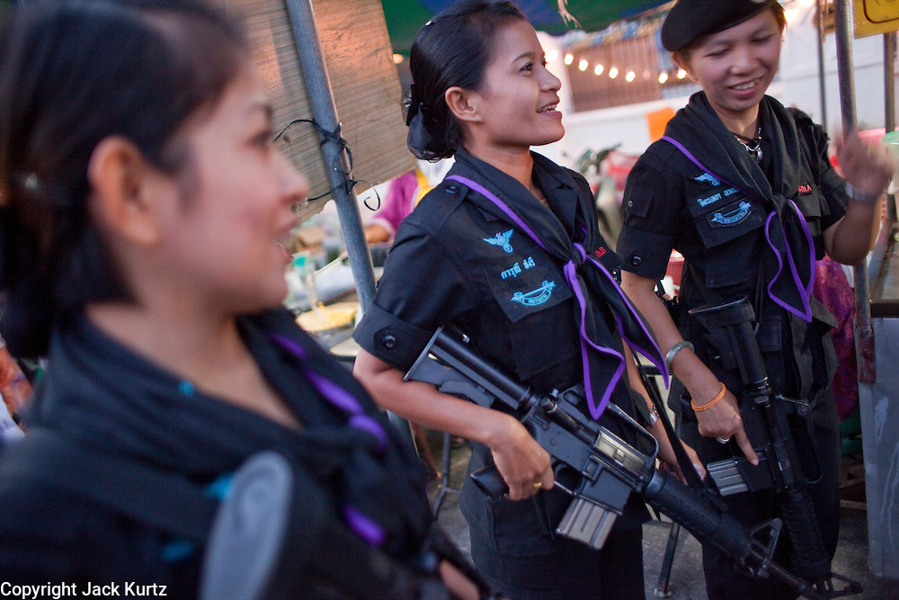 Sept. 29, 2009 -- YARANG, THAILAND: Members of the women's Ranger unit during a security sweep through the night market in Yarang, Thailand, Sept. 29. The 39 women in the 44th Army Ranger Regiment are the only Thai women seeing front line active duty against Moslem insurgents in Thailand's deep south provinces of Pattani, Narathiwat and Yala. All of the other women serving in Thai security services are employed as office and clerical workers. The Ranger women are based at the Ranger camp in the Buddhist village of Baan Trokbon in Sai Buri district of Pattani province. The unit was formed in 2006 after Muslims complained about the way Thai soldiers, all men, treated Muslim women at roadblocks and during security sweeps. The women are frequently called upon to back up Thai regular army units when they are expected to encounter a large number of Muslim women. At least two of the women have been killed by Muslim insurgents. The unit has both Muslim and Buddhist members. Many of the women in the unit joined after either their fathers or husbands were killed by insurgents.  Photo by Jack Kurtz / ZUMA Press