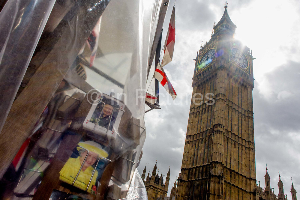 Queen Elizabeth appears on a rack of postcards in Westminster, central London. Recent showers has made the capital wet and so tourist trinkets and souvenirs have been covered with clear sheeting. We see the monarch the Queen, peering through the rain-soaked sheeting with the tall height of Elizabeth Tower where the bell known as Big Ben is housed. English flags hang limp after the soaking but sunlight is coming from behind the clock tower, the Gothic architecture of Victoria architect Pugin's building, the seat of parliamentary government in the UK.