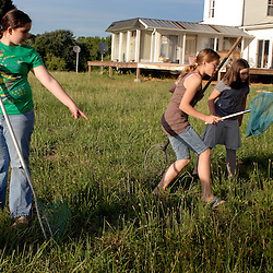 Jasmine Ammar, 11, points out the location of some dragonflies to Amber Rabie, 12, and her younger sister, Marie Ammar, 9, on the Ammar family farm during the night of the Great American Backyard Campout...Photo by Susana Raab..
