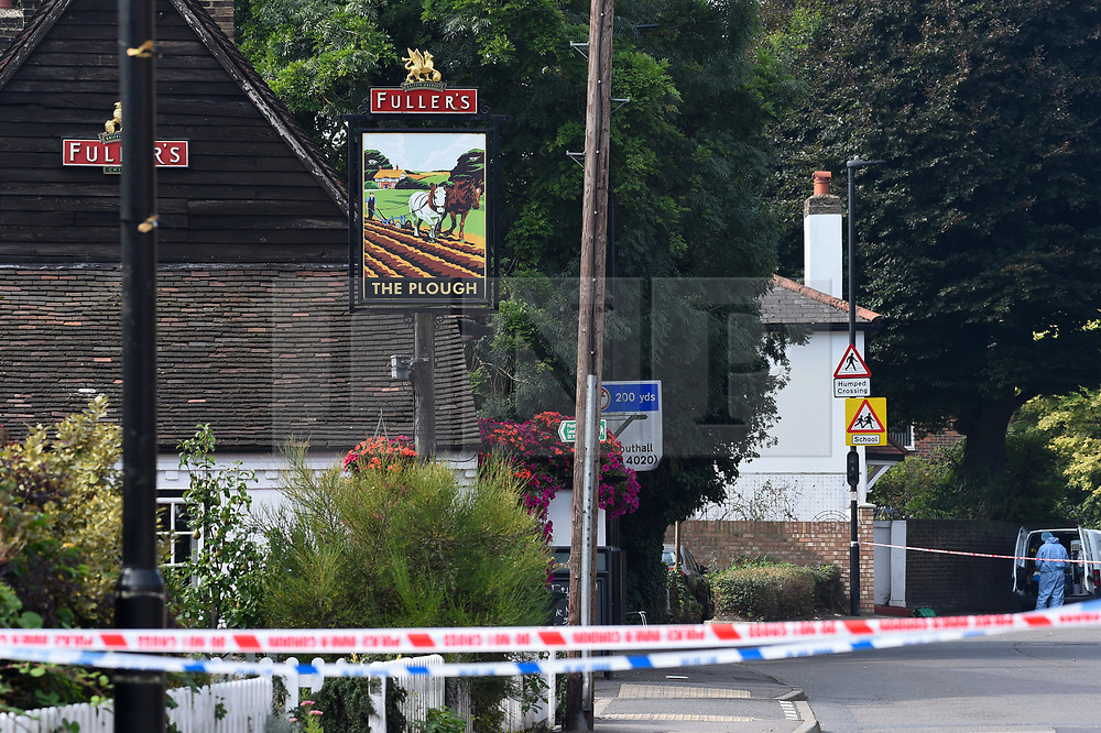 © Licensed to London News Pictures. 25/08/2019. SOUTHALL, UK.  A forensics officer at the scene adjacent to St Mary's Avenue near Southall in west London.  It is reported that a man in his 60s was stabbed outside The Plough pub (pictured left) on Tentelow Avenue in the early evening of 24 August and stumbled to nearby St Mary's Avenue to seek aid from a residence.  Police were called at 6.41pm, paramedics and air ambulance crews attended but the man passed away.  A man in his 30s has been arrested on suspicion of murder.  The investigation continues. Photo credit: Stephen Chung/LNP