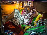 13 JULY 2013 - BANGKOK, THAILAND:   A tuk-tuk driver sleeps in the back of his tuk-tuk in Bangkok. Tuk-tuks are the three wheeled taxis found through out Asia.    PHOTO BY JACK KURTZ