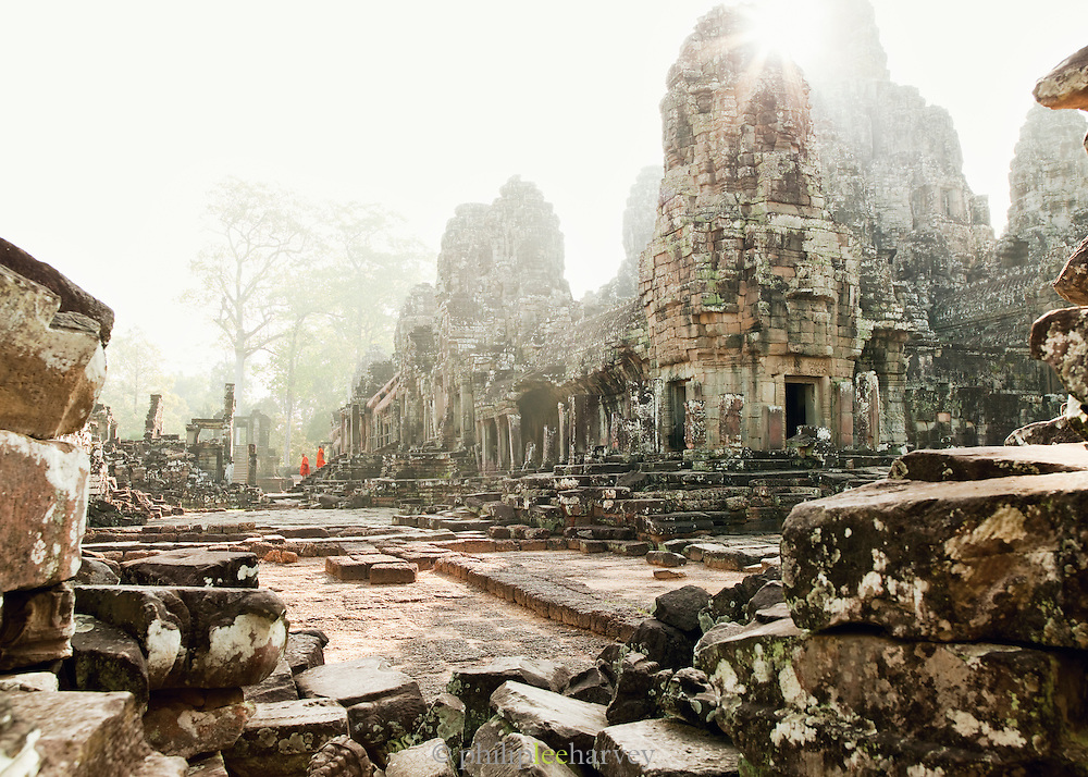 Buddhist monks walking out of the great Bayon Temple in the Angkor temple complex, Cambodia