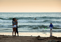 © Licensed to London News Pictures.23/07/2012. Caswell Bay, Gower Peninsula, Swansea, Wales, UK. A couple embrace and kiss, a child fishes for crabs, a surfer catches the last waves, all on the beach at Caswell Bay, Gower Peninsula, Near Swansea. Photo credit : Dave Warren/LNP