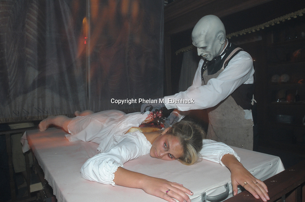 A ghoul operates on a woman's spine in the Body Collectors: Collections of the Past venue during a dress rehearsal of Universal Studios Florida's Halloween Horror Nights in Orlando, Fla., Tuesday, Sept. 16, 2008.