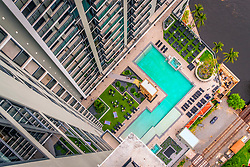 The pool deck at Society Las Olas, includes spas and daybeds, a hilly green area, a yoga lawn and a covered outside movie theater.