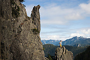 Gary Yngve looks out onto the surrounding peaks and valleys from a rock spire along the trail to Vesper Peak in the Mountain Loop Highway area of the Washington Cascades.