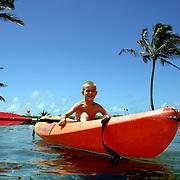 A young boy enjoys kayaking a saltwater lagoon at the Hyatt Regency Kauai Resort and Spa on Kauai.