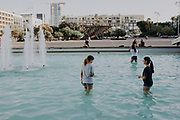 On a hot summer's, Children cool themselves in the water fountain in Rabin Square, Tel Aviv, Israel
