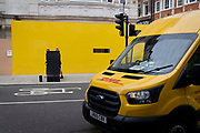 As two pedestrians merge with a traffic signal equipment box, a DHL courier van passes-by on Brook Street, W1, on 12th July 2021, in London, England.