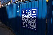 Blue QR code on a construction site hoarding on 30th March 2021 in Birmingham, United Kingdom. A QR code is a type of matrix barcode first designed in 1994 for the automotive industry in Japan. A barcode is a machine-readable optical label that contains information about the item to which it is attached.