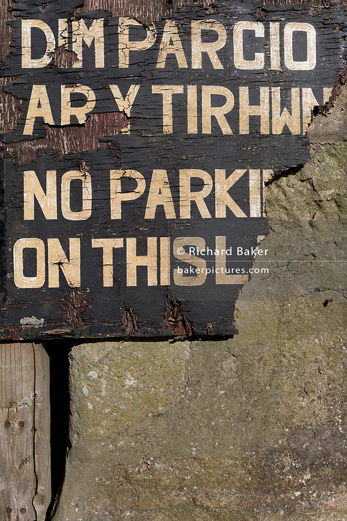 A broken and peeling sign warning in both the English and Welsh languages, of no parking  on 13th September 2018, in Barmouth, Gwynedd, Wales.
