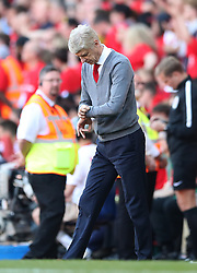 Arsenal manager Arsene Wenger checks his watch during the Premier League match at the Emirates Stadium, London.