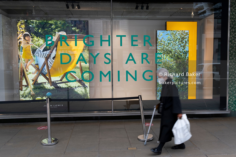 On the day that the UK government eased Covid restrictions to allow non-essential businesses such as shops, pubs, bars, gyms and hairdressers to re-open, an elderly shopper blurs past John Lewis on Oxford Street, on 12th April 2021, in London, England.