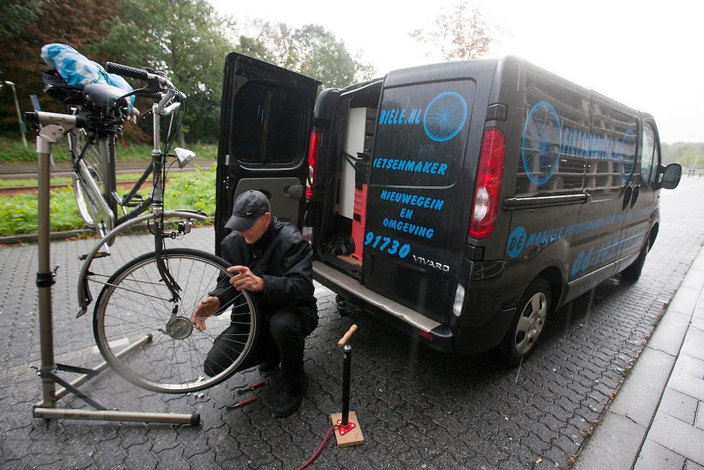 In de stromende regen repareert een mobiele fietsenmaker een fiets, vlakbij het transferium Westraven in Utrecht.<br /> <br /> A mechanic of a mobile bike repair is repairing a bike with a flat tyre nearby a transferium in Utrecht.