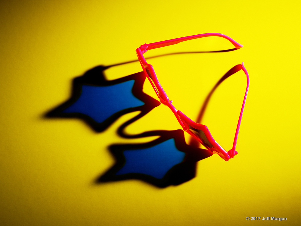 Still life of crazy, star shaped sunglasses with dramatic shadow.
