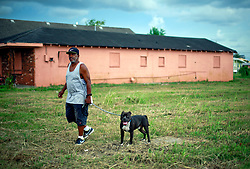 29 August 2014. Lower 9th Ward, New Orleans, Louisiana.<br /> Hurricane Katrina memorial 9 years later. <br /> A Katrina survivor takes his dog for a walk on a vacant lot of a home on the 9th anniversary of the storm that devastated the region.<br /> Photo; Charlie Varley/varleypix.com
