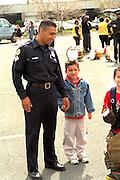 Policeman holding boy's hand age 32 and 7  Cinco de Mayo.  St Paul Minnesota USA