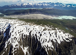 Little remains of the Burroughs Glacier (center). In the foreground, are the snow-covered tops of Minnesota Ridge. On the other side of Burroughs Glacier are the Bruce Hills, followed by Wachusett Inlet. The far side of the inlet are the mountains of Idaho Ridge including: Mount Kloh Kutz, Mount Cadell, Mount Merriam and Mount Wordie. In the very distant upper part of the image, mountains of the Fairweather Range can be seen.<br /> <br /> Glacier Bay National Park is located in southeast Alaska. Known for its spectacular tidewater glaciers, icefields, and tall costal mountains, the park is also an important marine wilderness area. The park a popular destination for cruise ships, is also known for its sea kayaking and wildlife viewing opportunities. <br /> <br /> Glacier Bay National Park is home to humpback whales which feed in the park's protected waters during the summer, both black and grizzly bears, moose, wolves, sea otters, harbor seals, steller's sea lions and numerous species of sea birds. <br /> <br /> The dynamically changing park, known for its large, contiguous, intact ecosystems, is a United Nations biosphere reserve and a UNESCO World Heritage site.