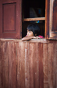 A young girl gazes out of the window at Inle Lake in Shan State, Myanmar