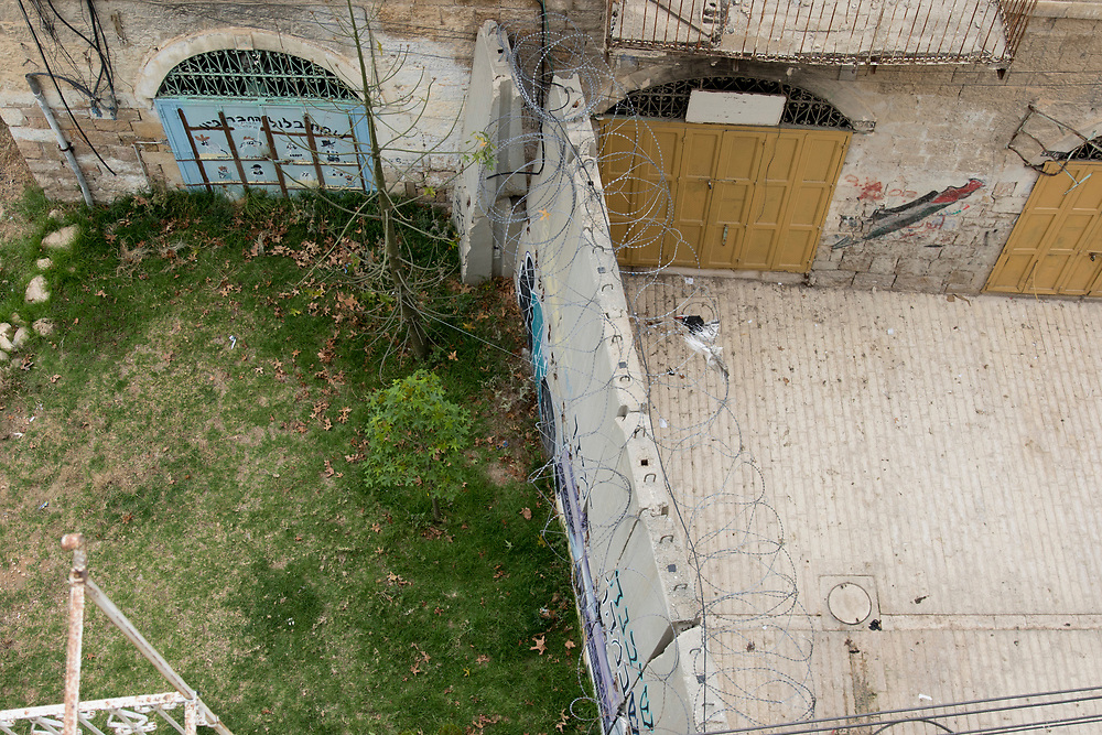 A barrier divides a street, preventing Palestinians from using one side