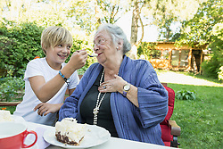 Grandson feeding his grandmother with cream cake