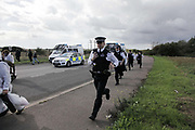 Police are stuck in their vehicles behind the human chain of activists and have to make their way pass to get ahead of the them on foot. They are now on the road heading to the refinery and the blockade held by a group of women locked onto two vans. <br /> <br /> Crude Oil Awakening is a coalition of climate change activist groups. On Saturday Oct 16 they shut the only entrance to Coryton oil refinery in Essex, UK with the aim of highlighting the issues of climate change and the burning of fossil fuels. The blockade meant that a great number of trucks with oil were not able to leave the refinary during the day of action.