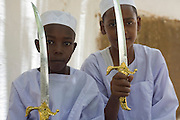 Two young boys hold up their plastic swords during a lull in the first-ever international Conference on Womens' Challenge in Darfur, arranged in a compound belonging to the Govenor of North Darfur in Al Fasher (also spelled, Al-Fashir) where the women from remote parts of Sudan gathered to discuss peace and political issues.