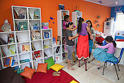 A group of children putting on their stilts in the community library, Biblioteca Comunitaria do Arquipelago, Porte Alegre, Brazil. <br /> <br /> Once a week the children have a music and poetry session where they go out in to the community on stilts singing, playing music and reciting poetry.<br /> <br /> Cirandar is working in partnership with  C&A and C&A Instituto to implement a network of Community Libraries in eight communities of Porto Alegre.