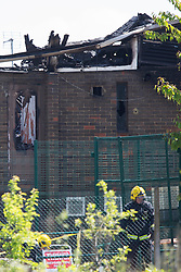 © licensed to London News Pictures. London, UK 05/06/2013. Police officers and fire brigade checking the remainings of the Somali Bravanese Welfare Association in Muswell Hill, London. Police reports suggesting that The Islamic Community Centre had extensive damage by a fire in the early morning. The cause of the fire is currently under investigation and is being treated as suspicious at this stage as an EDL graffiti has been found in the building and media reports suggest that the incident might have links to the Woolwich attack. Photo credit: Tolga Akmen/LNP