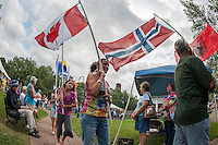 Canada, Norway and Albania were among the many countries represented by local residents as the Parade of International Flags marches through downtown Laconia during the annual Multicultural Day festivities.  (Karen Bobotas/for the Laconia Daily Sun)
