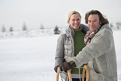 Portrait of couple standing with sledge, smiling, Bavaria, Germany