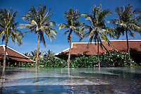 A series of swimming pools and water features lined with palm trees lead down to the beach at the Nam Hai Resort, Hoi An, Vietnam.