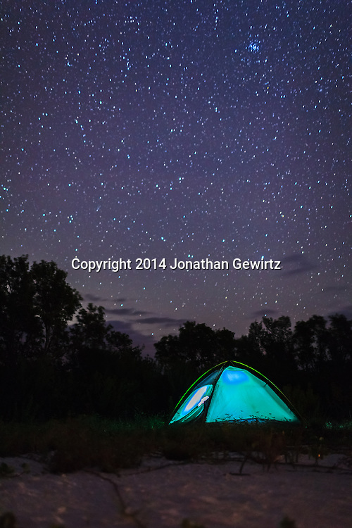 A tent illuminated by internal light glows under a magnificent starry night sky on the beach at East Cape Sable, on Florida Bay at the southern end of Everglades National Park. WATERMARKS WILL NOT APPEAR ON PRINTS OR LICENSED IMAGES.