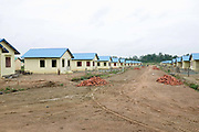 New concrete houses in a mostly-empty, half-constructed resettlement site situated along a main road in Steung Treng province in north-eastern Cambodia. 5000 people from 20 villages are being evicted from their homes to make way for a controversial huge new hydropower dam: 'Lower Sesan 2', which will flood an area of more than 33,000 square hectares. Communities in this rural region are seeing their traditional self-sufficient farming and fishing lifestyle disrupted by dam building and the impact of climate change on crops, water quality and fish stocks.