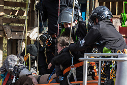 Denham, UK. 22nd March, 2021. Bailiffs from the National Eviction Team (NET) work to remove two anti-HS2 activists who are locked together from a makeshift tower in Denham Country Park where they had been seeking to delay electricity pylon relocation works by Babcock in connection with the high-speed rail project.