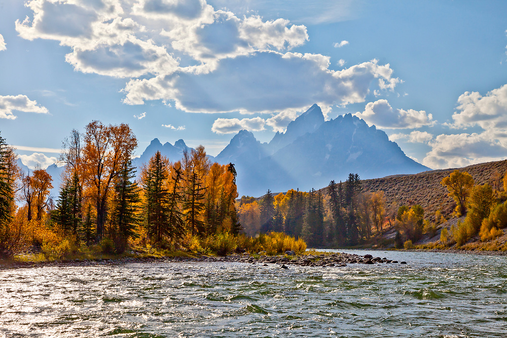 Waters edge view from a raft on the Snake River with the Teton Mountain Range in Teton National Forest on beautiful calm autumn day. Licensing and Open Editions